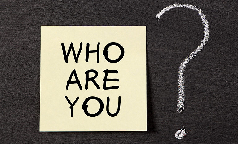 """post-it that asks brands, """"who are you?"""" with a question mark written in chalk to the right of the paper"""