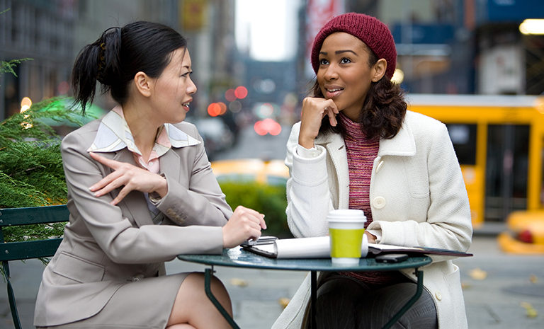 two women sitting at a table wearing business attire outside in a city environment with a cup of coffee and notebook