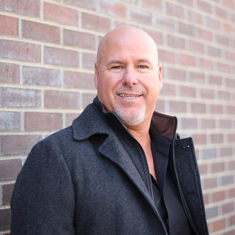portrait of John Gagne, CEO and founder of Elevation Ten Thousand, wearing a gray coat against a brick background