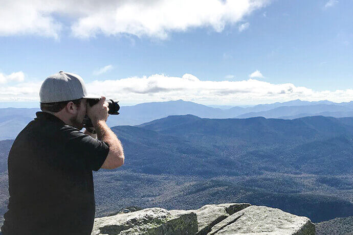 photo of man in black shirt and gray hat taking pictures with camera of a scenic mountain landscape