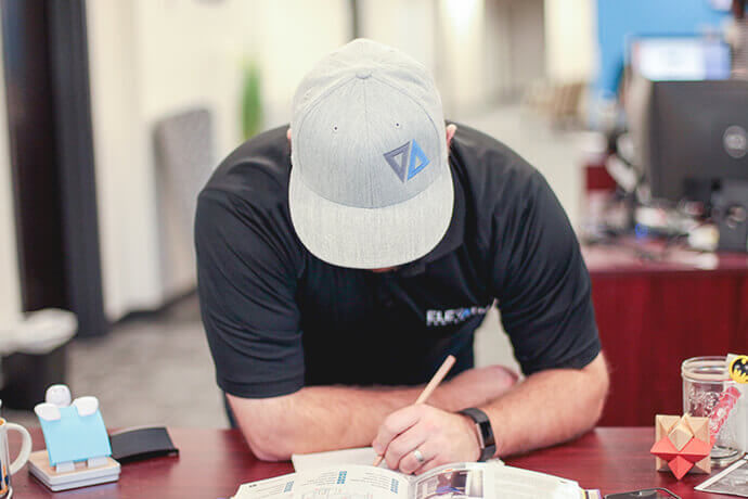 person wearing black Elevation Ten Thousand branded shirt and gray hat writing on paper at a desk in an office