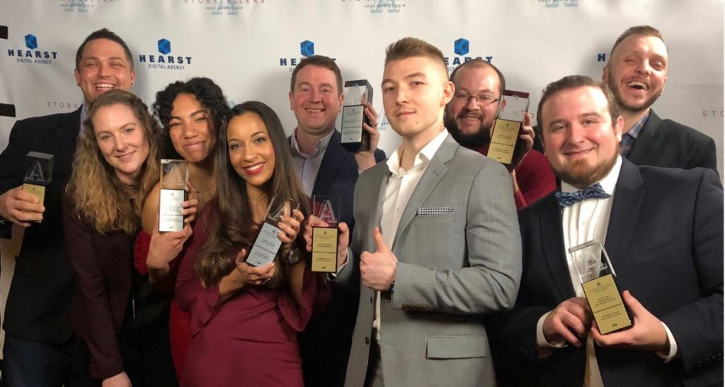 Elevation Ten Thousand marketing team holding their Addy award trophies