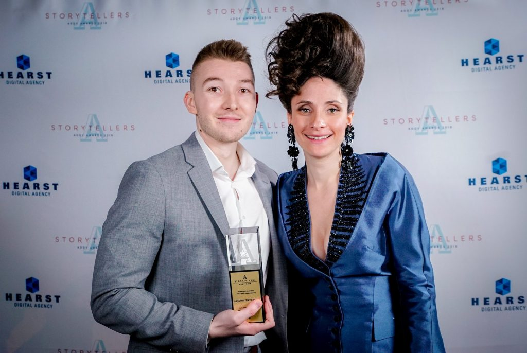 Adult man holding Addy award trophy next to an adult woman