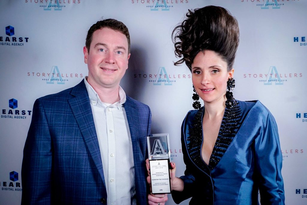 Adult man and woman standing in front of a branded background holding an Addy Award trophy