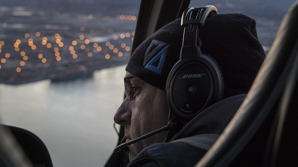 Close up shot of man wearing Bose headphones looking out a helicopter windshield