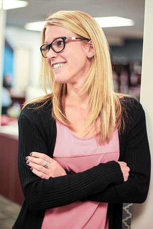 woman with glasses smiling with her arms crossed looking to the left, wearing a black cardigan and pink shirt