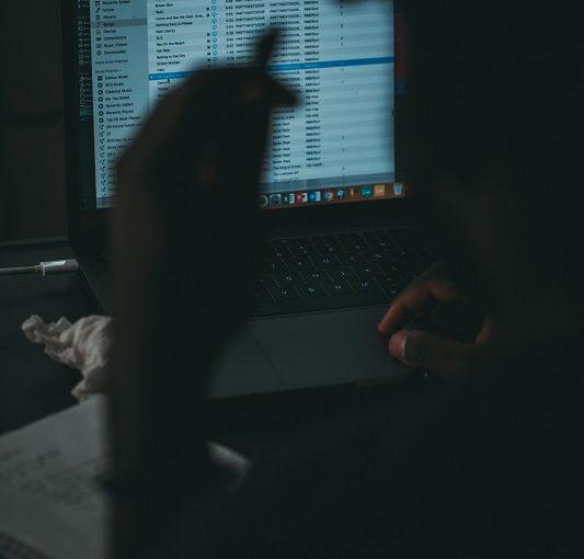 man sitting in dark room using a laptop