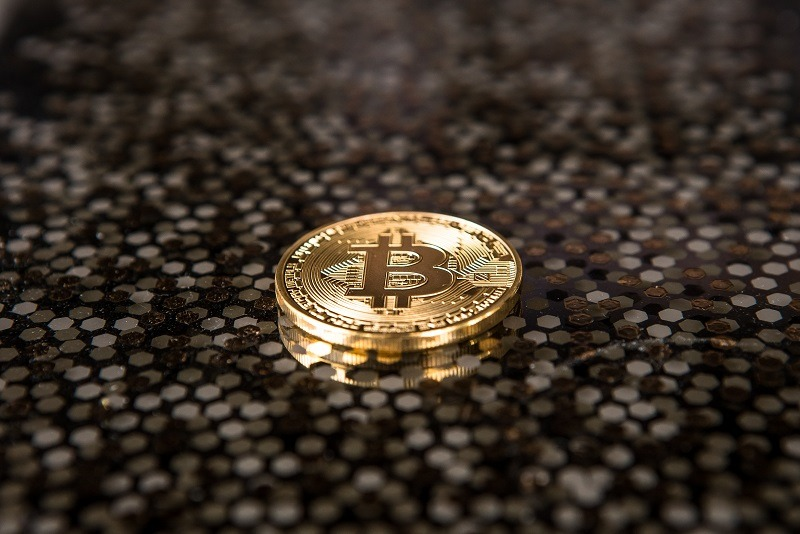 gold Bitcoin placed on a speckled brown floor