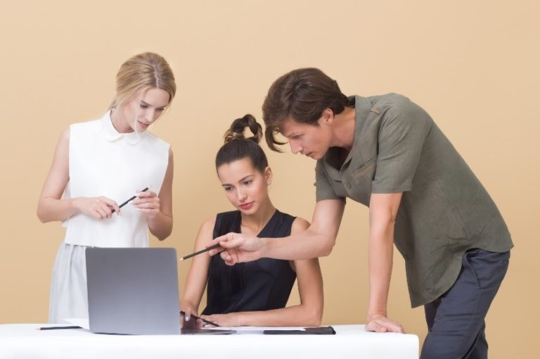 Two women and a man looking at a laptop critiquing the work