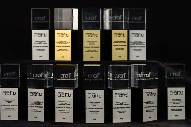 five ADDY Awards stacked on top of a row of seven ADDY Awards in front of a black background