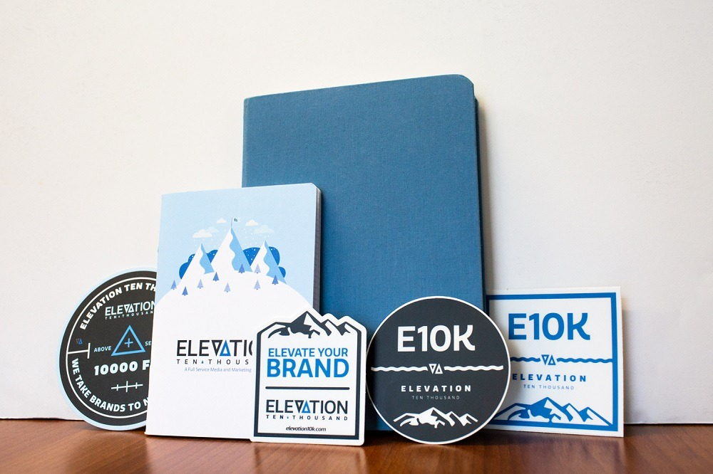 Branded Elevation Ten Thousand notebooks, coasters, and stickers on a wood table in front of a white backdrop