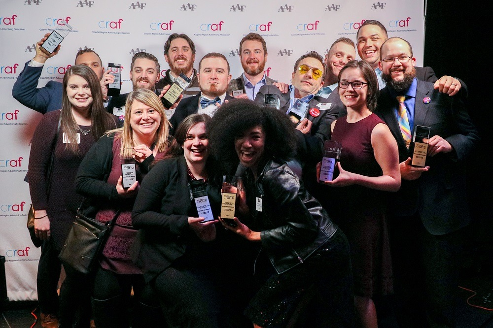 Team photo of 14 adults in dress attire standing in front of the Craf backdrop holding 12 ADDY awards