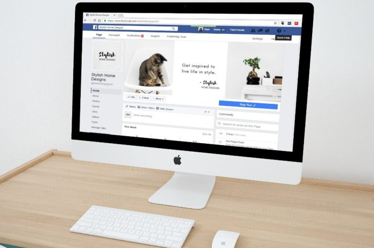 white Mac on a wood desk with a Facebook Business Page loaded on the screen