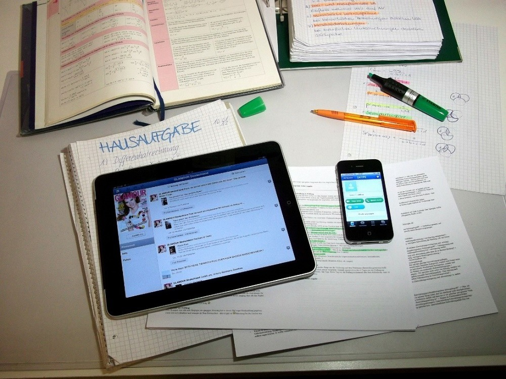 Large white desk with notebooks and notes with a large black iPad showing a Business Facebook Page and an iPhone