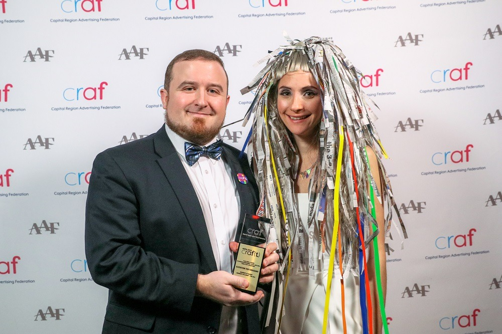 two adults in dress attire holding a gold ADDY award standing in front of the Craf backdrop at the ADDY awards