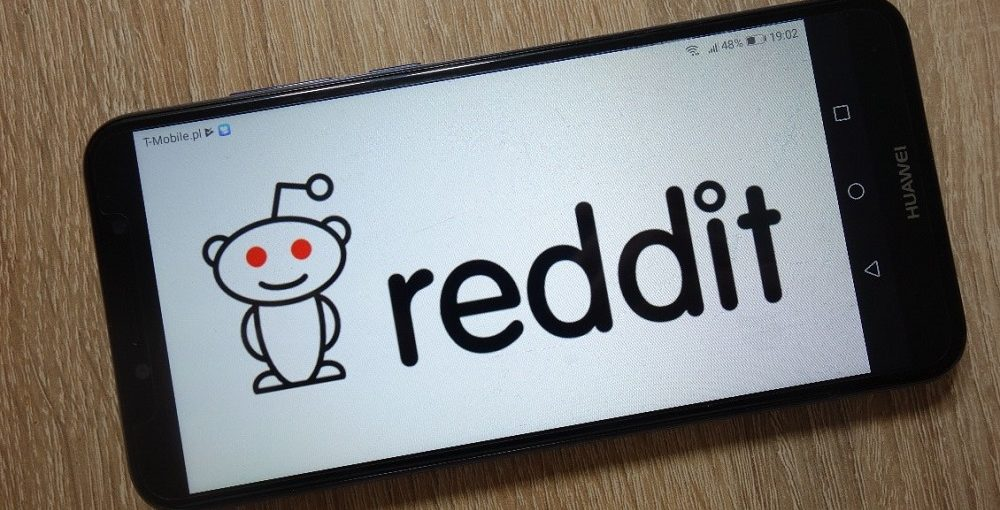 black cellphone on wood table with Reddit logo on screen