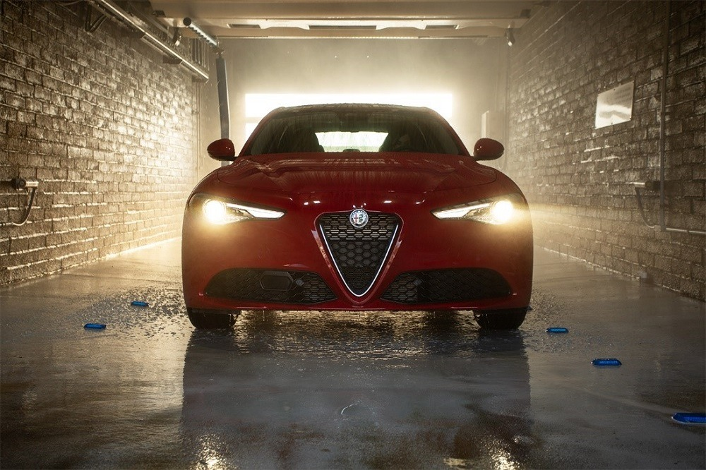 new red 2019 Alfa Romeo Giulia Ti with LED headlights on inside a brick carwash tunnel