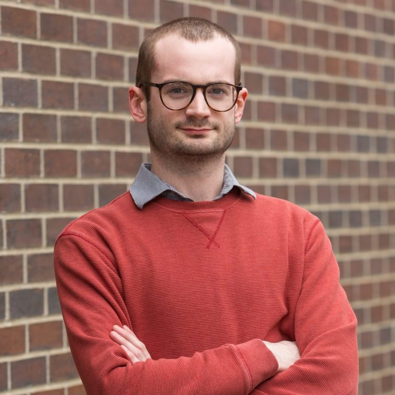 portrait of Shea Lynch, senior SEO analyst at Elevation Ten Thousand with his arms crossed leaning against a brick wall