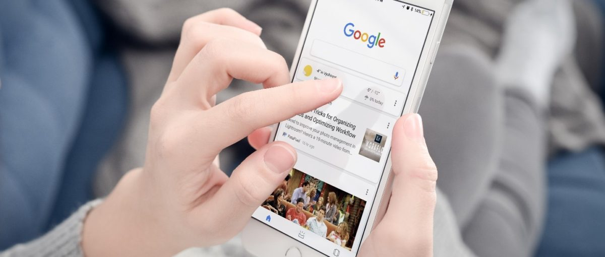 woman holding white smartphone looking at a Google search results page