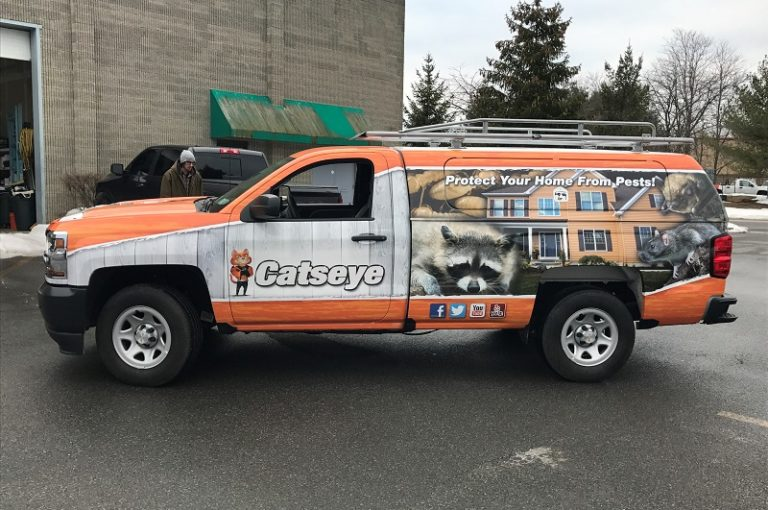 commercial truck with a full vehicle wrap displaying bright colors, brand logo, and a design of a home with nuisance wildlife