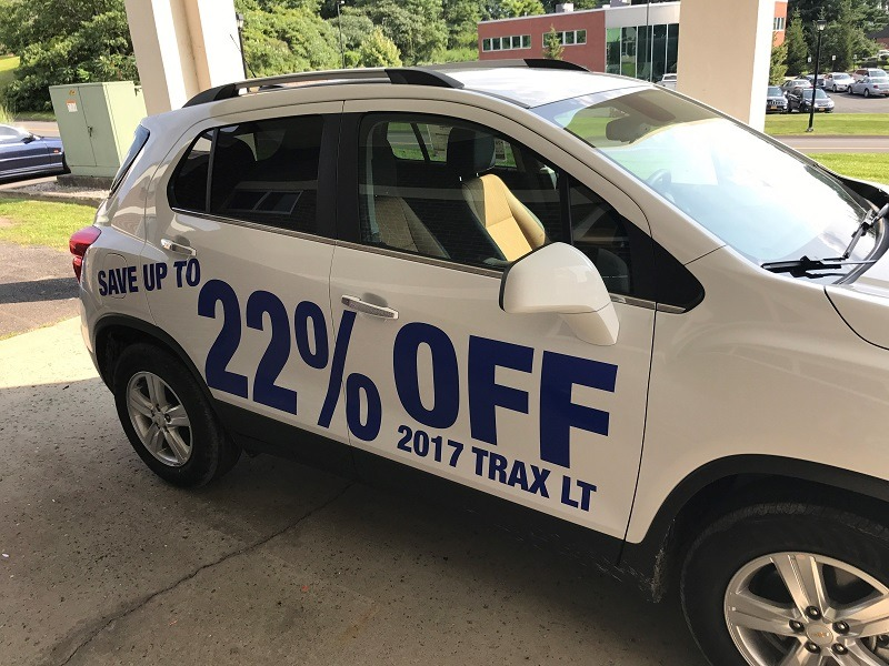 white crossover SUV with dark blue vinyl graphics displaying percentage savings for the vehicle