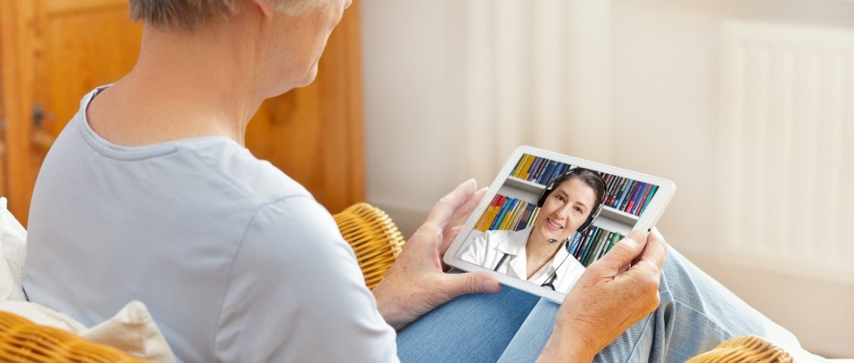 adult woman sitting in a brown wicker chair holding a white tablet on a video call with a medical professional
