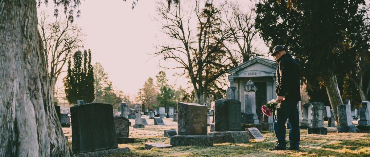 Man dressed in black jacket with flowers in hand standing in graveyard