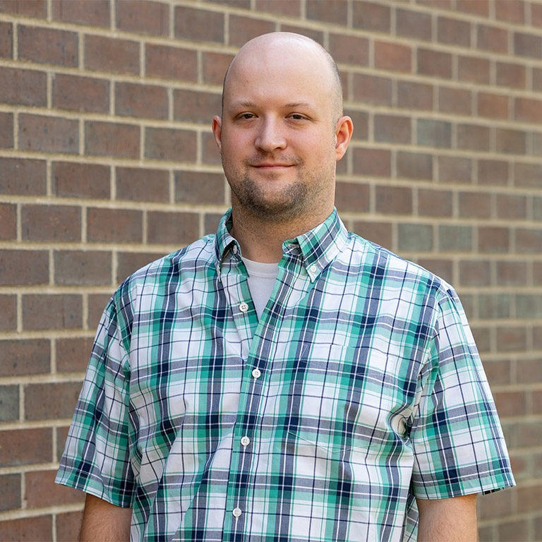 adult male wearing a blue and white plaid shirt standing in front of a brick wall
