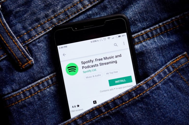 blue jeans with black smartphone in a pocket with the Spotify application open in the play store