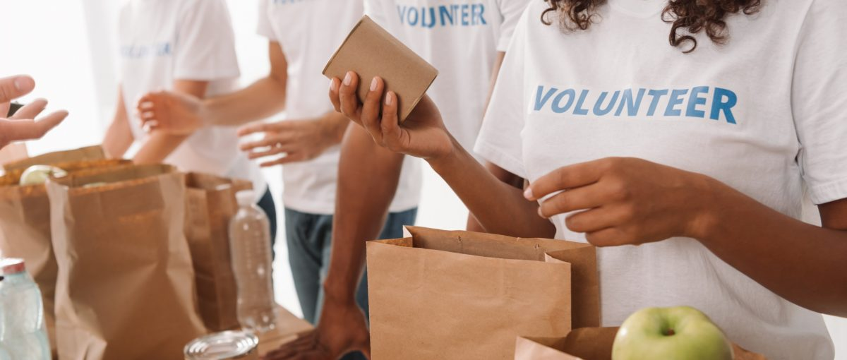 group of adults wearing white shirts with blue volunteer lettering bagging groceries for charity