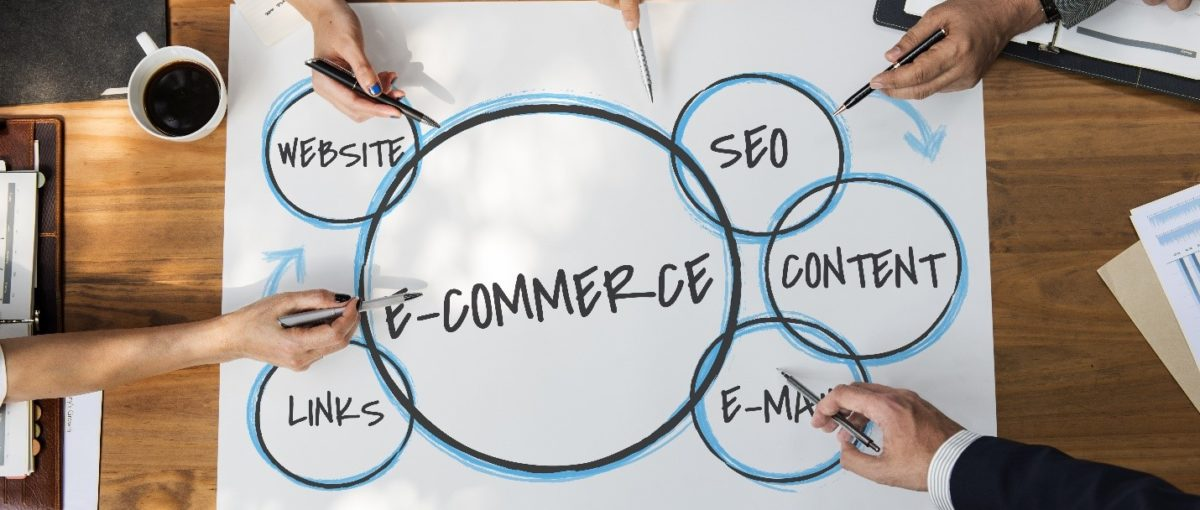 business professionals at a brown wooden table pointing to the important parts of an SEO strategy for e-commerce websites written on white construction paper