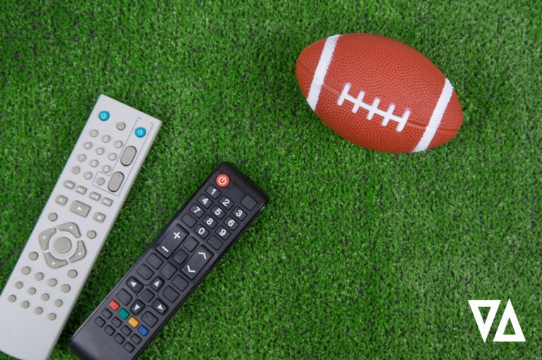 gray and black television remotes placed on green turf close to a brown football with white laces and stripes