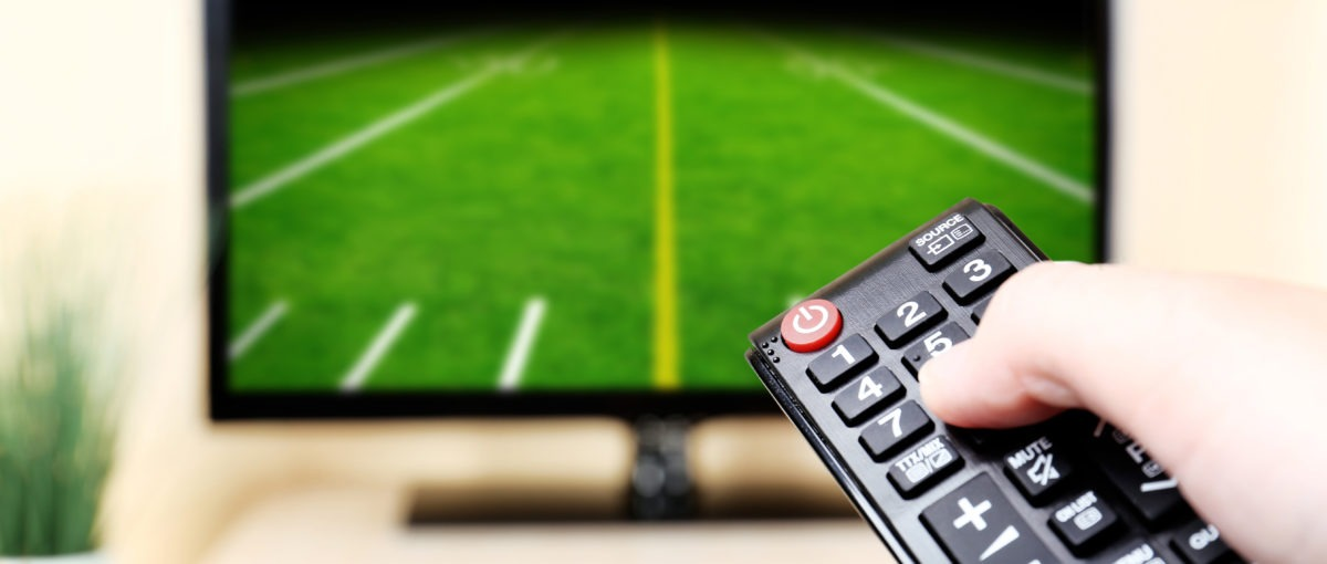adult hand holding a black remote pointed at a black television with a football field on the screen