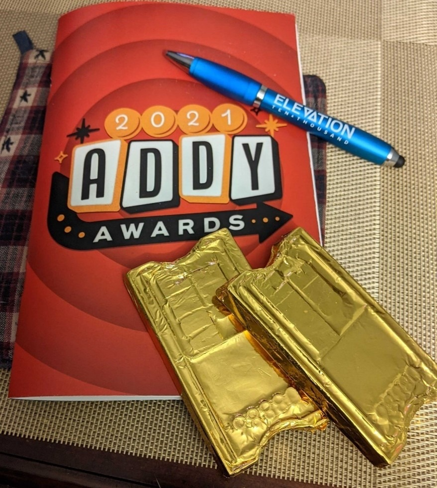 gold-wrapped chocolate bars shaped like ticket stubs resting on a 2021 ADDY Awards program with a blue pen