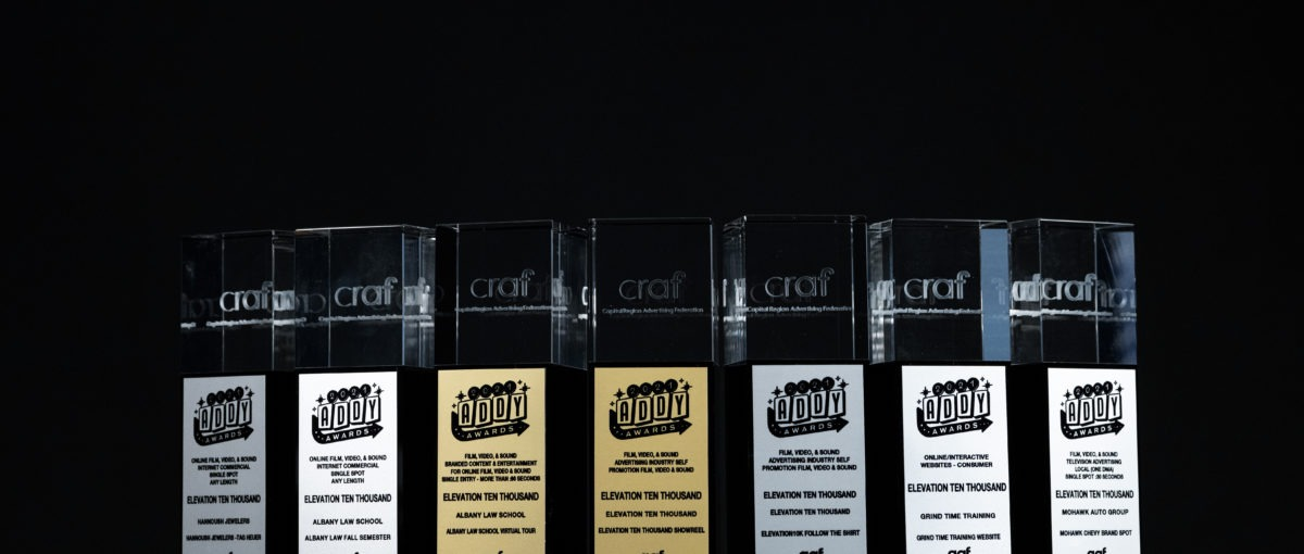 five silver and two gold Capital Region American Advertising Awards trophies on a black stand in front of a black background